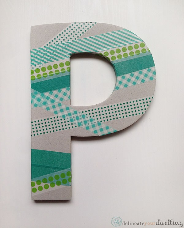 Learn how to make an adorable DIY Washi Tape Letter wall decor to hang in your child's bedroom. We used so many fun shades of green and love it. Delineate Your Dwelling #washitapecraft #boywalldecor