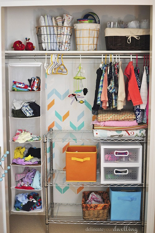 How to transform a dull unorganized closet into a fun paint herringbone patterned Kid's Closet. Such a huge improvement, check out this easy makeover. Delineate Your Dwelling #kidscloset #paintedherringbone