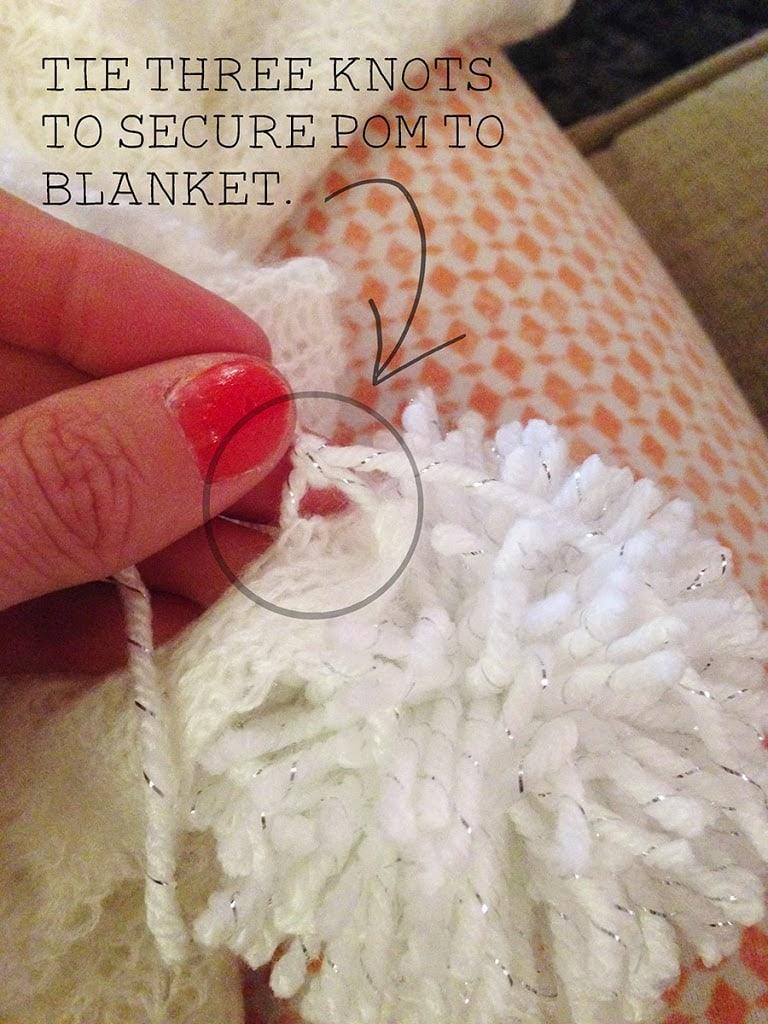 Sew a pom pom to a blanket