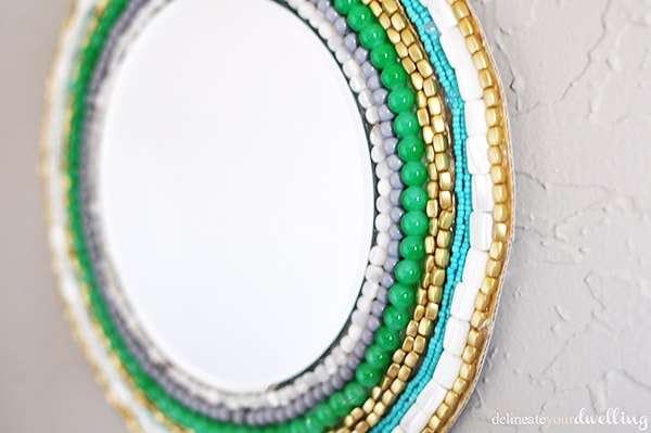 Learn how to create a stunning Round Beaded Wall Mirror using only a few simple materials! Hang this colorful DIY Mirror on the wall to admire every day. Delineate Your Dwelling #beadedwallmirror #roundwallmirror #DIYbeadedmirror