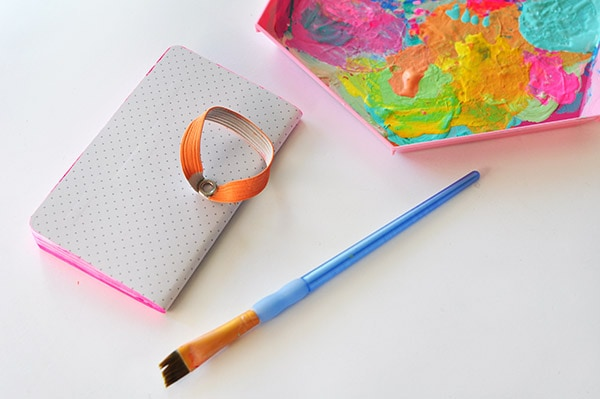 Learn how to create a simple colorful DIY Painted Notebook edge! This is a fun DIY craft project for children and adults alike.  Check out all the ways it brightens up any old notebook or notepad. Delineate Your Dwelling #DIYpaintednotebook #AcrylicPaintNotebook #paintednotebook