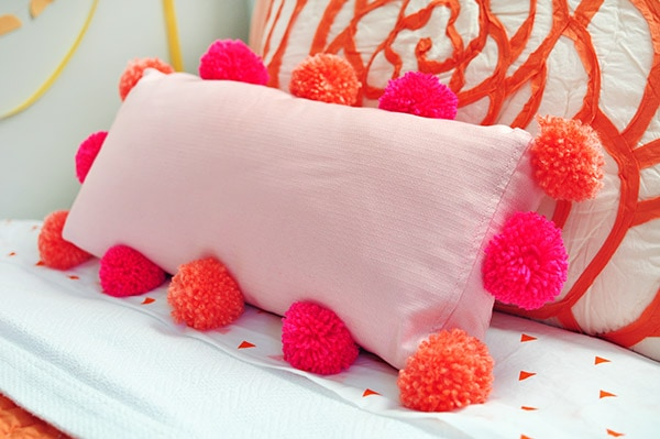 Instructions on how to make and add DIY Pom Poms to an Existing Pillow in your home.  It is much easier than you would think! Add a little fun texture to your pillows today. Delineate Your Dwelling #pompompillow #DIYpompompillow