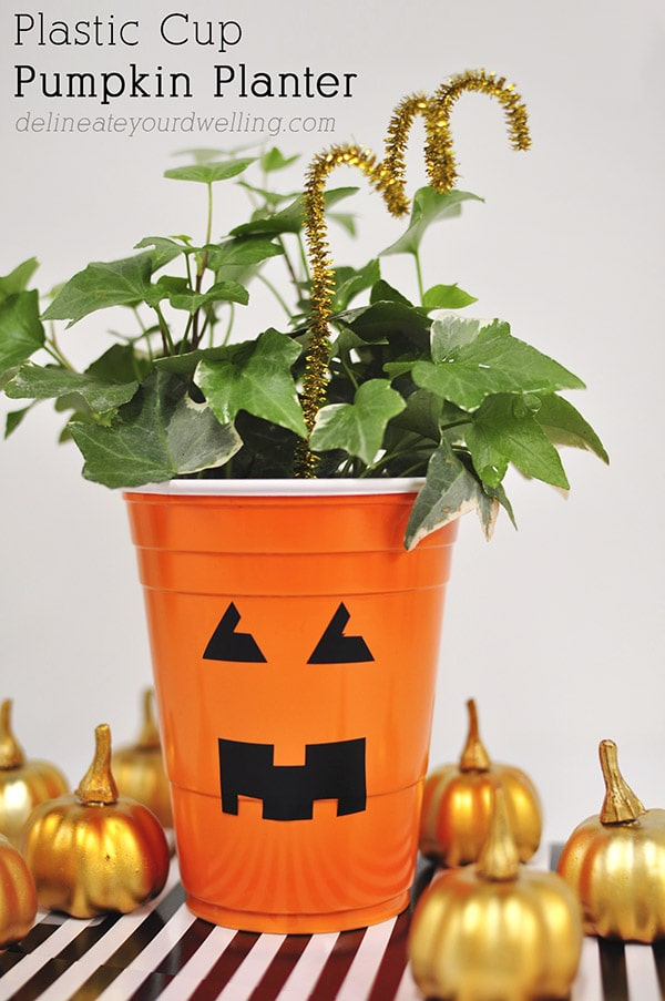 See how to take a simple plastic cup and transform it into a fun festive Pumpkin Planter! You can make this quick DIY Face Vase craft with your kids, too! Delineate Your Dwelling #pumpkinplanter #plasticcupplanter #kidcraftfall #falltimecraft