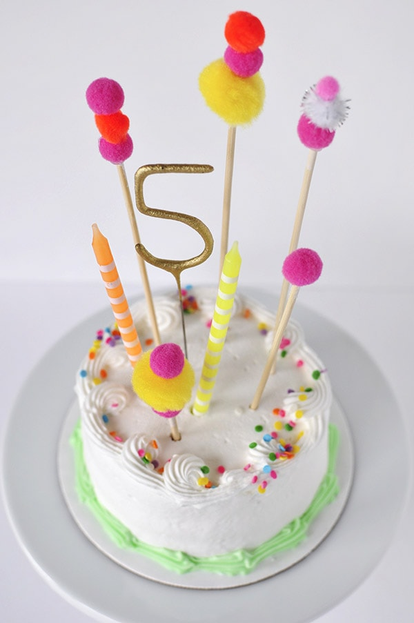 Adorable and simple, see how to create this Pom Pom Birthday Cake Topper for your next party!  Fun Banner Cake Toppers make celebrations so much more fun and they are easy to add to any dessert. Delineate Your Dwelling #pompombirthdaycake #pompomcaketopper #birthdaytopper #pompomcake
