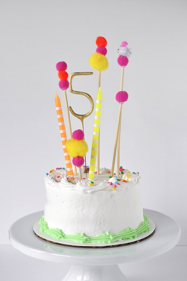 Adorable and simple, see how to make this Pom Pom Birthday Cake Topper for your next party! Fun Banner Cake Toppers make celebrations so much more fun and they are easy to add to any dessert. Delineate Your Dwelling #caketopper #pompomcraft