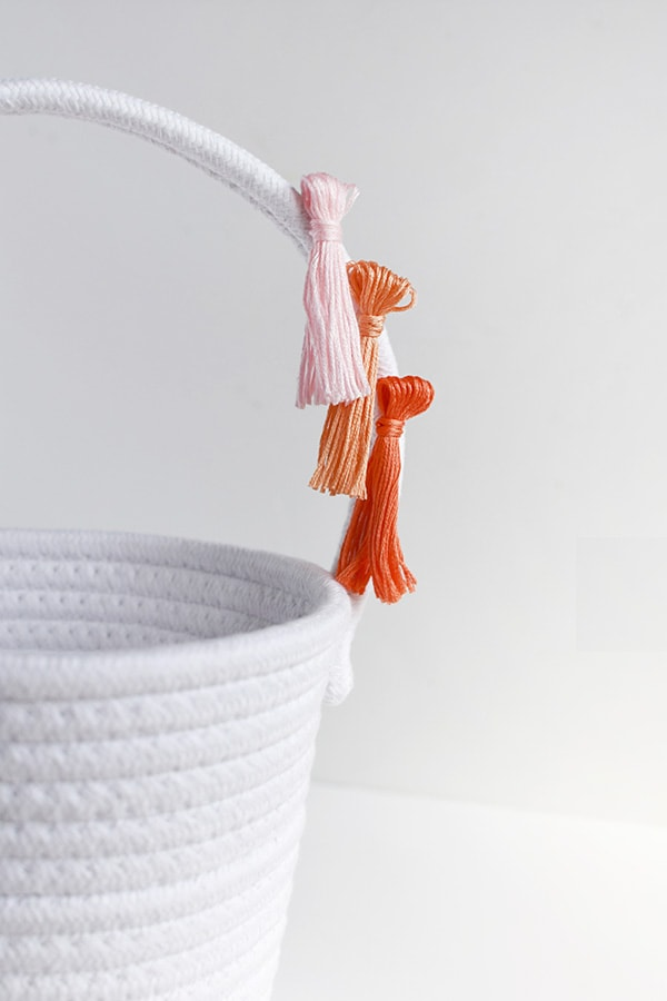 First, learn how to make tassels using Embroidery Floss. Then apply those tassels to any type of basket, making a simple and fun DIY Tassel Easter Basket for Easter this year! Delineate Your Dwelling #easterbasketDIY #tasselbasket #DIYEasterBasket #DIYEaster