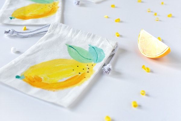 Learn how to paint fun refreshingly easy DIY Painted Lemon Bags! They are great to give as gift bags, teacher gifts or just told tasty treats. Perfect for summer fun. Delineate Your Dwelling #paintlemon #lemonbag #fruitcraft