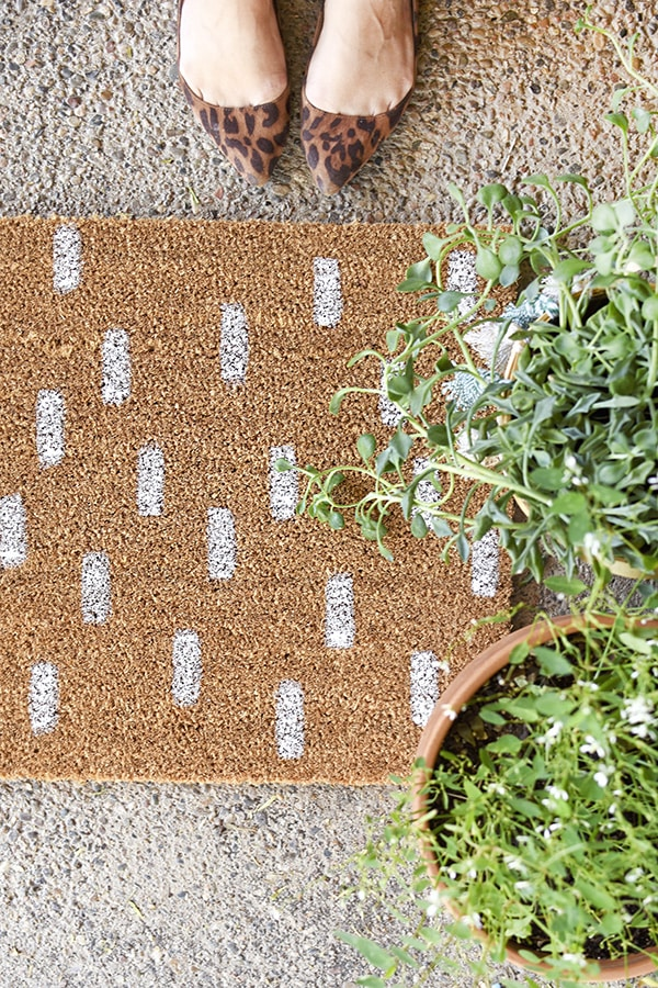 15 minute Painted DIY White Dash Doormat - Learn how to transform a plain doormat into a gorgeous Painted DIY White Dash Doormat.  It's so simple and keeps you trendy with a simple dash pattern. Delineate Your Dwelling