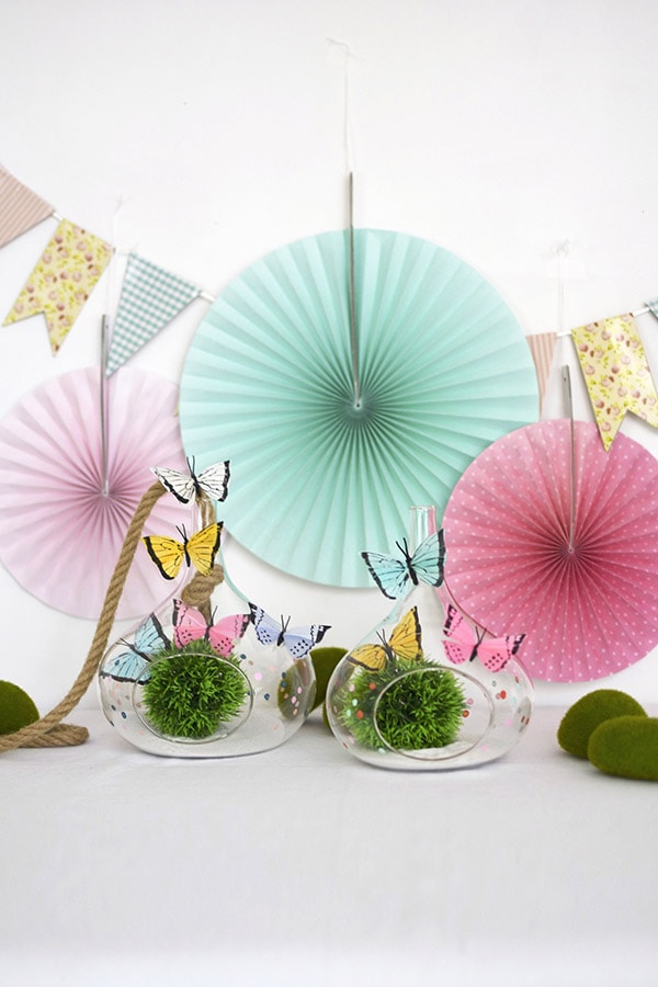 Learn how to make a DIY butterfly terrarium this Spring season! Using colorful faux butterflies, gorgeous glass terrariums and some fun moss balls the sky is the limit to the fun you can have. Delineate Your Dwelling #DIYterrarium #butterflyterrarium