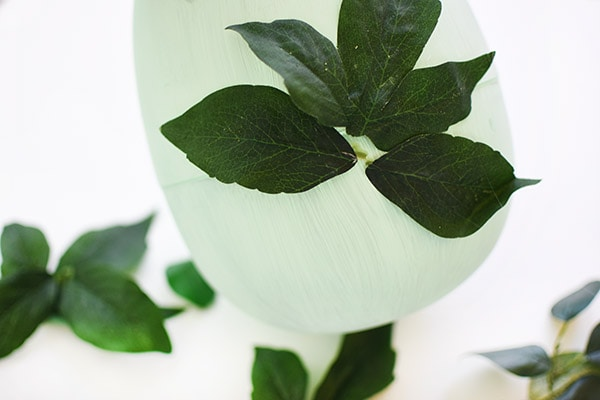 Learn how to make gorgeous Greenery Easter Egg Decor : Adding leaves.