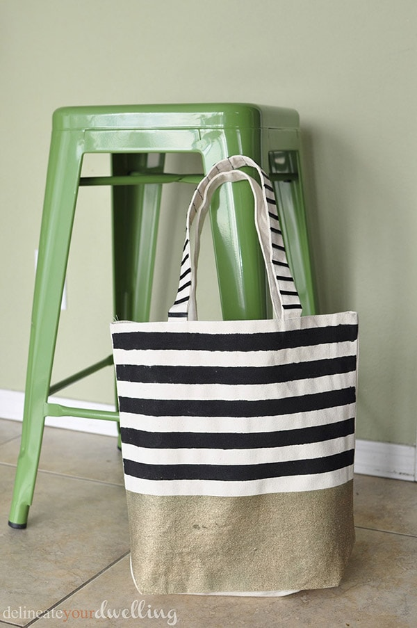 Learn how to create a gorgeous DIY Striped West Elm inspired tote bag! Perfect for carrying your miscellaneous items around in style. Delineate Your Dwelling #stripedtotebag #canvastotebag #DIYcanvastote