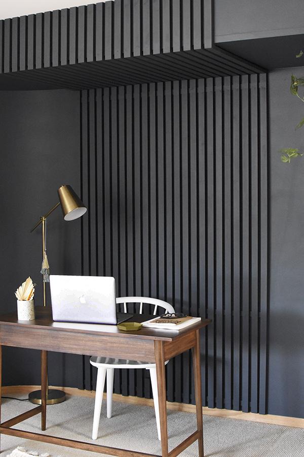 Dark blue painted wooden slat wall